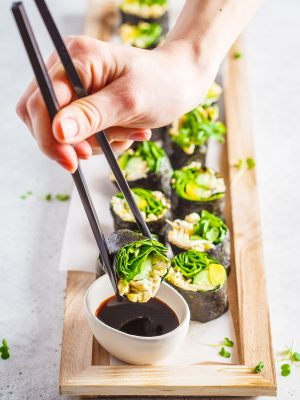 Vegan green sushi rolls with avocado, sprouts, cucumber and nori